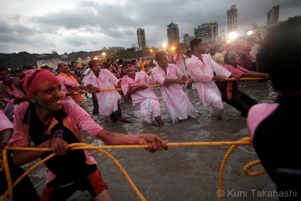 Men pull an Ganesha idol in ocean for immersion in Mumbai, India on Sep 22, 2010 on the last day of Ganpati festival. The 10-day hindu festival, celebrating the birthday of Lord Ganesha who is widely worshiped as the god of wisdom, prosperity and good fortune, attracts tens of thousands people.<br /> Photo by Kuni Takahashi