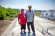 Rudolf (52) and his wife Jana standing on the new foundation of their becoming house (2013). The village of Rankovce, close to Kosice in eastern Slovakia. The foundation ETP Slovakia has a project in Rankovce setting up micro-loan funds for the local Roma community. Loans from this fund will enable families to build their own low-cost brick homes, on land they own. The families are committed to radically improve their living conditions.