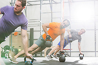 Men exercising with kettlebells in crossfit gym