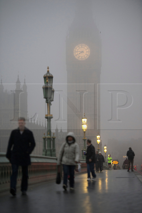 © London News Pictures. 21/01/2014. London, UK.  Commuters pass over Westminster Bridge in front of the Houses of Parliament in Westminster shrouded in fog early morning in central London on January 21, 2014. Photo credit: Ben Cawthra/LNP