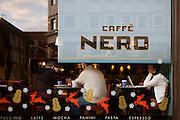 Coffee drinkers sit in the seasonally Xmas decorated window of a branch of Caffe Nero in the weeks before Christmas.