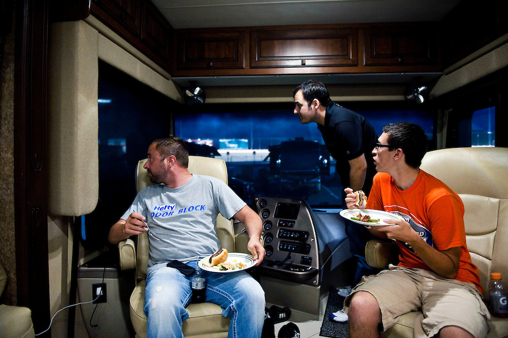 NEWTON, IOWA. -AUG. 1, 2014: NASCAR driver Eric McClure, left, NASCAR driver Hal Martin, center, and Eric Bjurstrom, right, watch a race on the track behind them while enjoying a meal after the day's practice for the NASCAR Nationwide Series auto race at Iowa Speedway Friday, Aug. 1, 2014. Lauren Justice for The New York Times