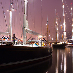 Large sailing yachts docked at night in Newport Harbor, Rhode Island.