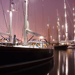 Large sailing yachts docked at night in Newport Harbor, Rhode Island.