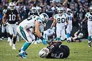 Oakland Raiders wide receiver Michael Crabtree (15) makes a catch late in the fourth quarter and has his helmet ripped off by Carolina Panthers outside linebacker A.J. Klein (56) at Oakland Coliseum in Oakland, Calif., on November 27, 2016. (Stan Olszewski/Special to S.F. Examiner)