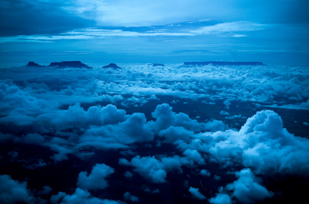 "A chain of ""tepui"", the Pemón Indian word that means ""mountain"",  in Venezuela's Gran Sabana peak through the clouds as seen from 9,500 feet above sea level.  (left to right : Tramén-Ilú-Karaurín-Yuraní-Kukenán-Roraima) *Pending Expert Confirmation*"