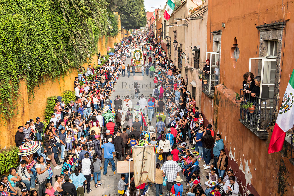 A religious procession carries a statue of St Michael through the historic district during the week long fiesta of the patron saint Saint Michael September 30, 2017 in San Miguel de Allende, Mexico.