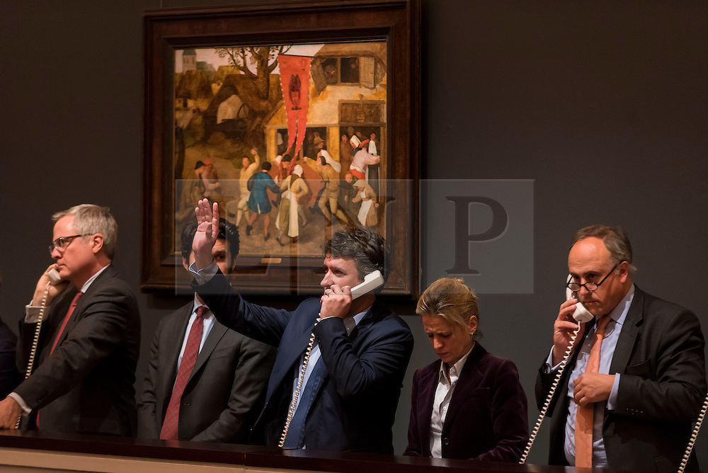 """© Licensed to London News Pictures. 07/12/2016. London, UK. Sotheby's staff make bids on behalf of telephone clients in front of """"A Village Kermesse"""" by Circle of Pieter Bruegel the Elder sold for a hammer price of GBP125k (est. GBP 80-120k),    at the Old Masters Evening Sale at Sotheby's in New Bond Street. Photo credit : Stephen Chung/LNP"""