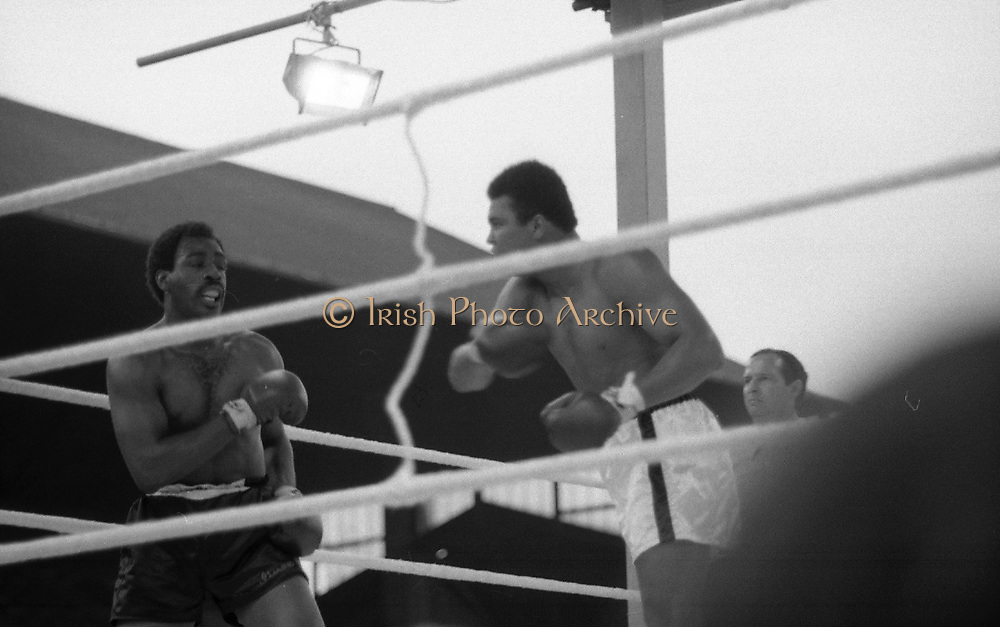 Ali vs Lewis Fight, Croke Park,Dublin.<br /> 1972.<br /> 19.07.1972.<br /> 07.19.1972.<br /> 19th July 1972.<br /> As part of his built up for a World Championship attempt against the current champion, 'Smokin' Joe Frazier,Muhammad Ali fought Al 'Blue' Lewis at Croke Park,Dublin,Ireland. Muhammad Ali won the fight with a TKO when the fight was stopped in the eleventh round.<br /> <br /> Image of Ali as he drives Lewis back onto the ropes in this onslaught.