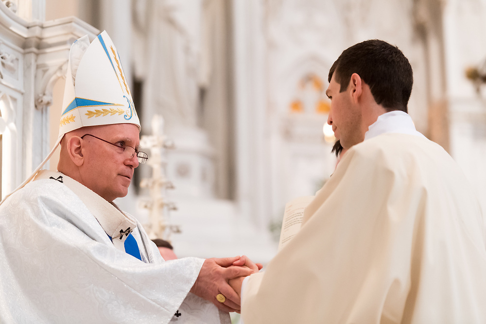 DENVER, CO - MAY 13: Denver Archbishop Samuel Aquila holds Shaun Galvin's hands for the promise of respect and obedience for his ordination of the priesthood at the Cathedral Basilica of the Immaculate Conception on May 13, 2017, in Denver, Colorado. (Photo by Daniel Petty/for Denver Catholic)