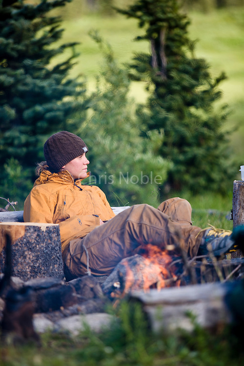 Conservation student Blakely Adkins takes a break  beside a campfire while hiking the Kuthai Trail during a summer program run by Round River Conservation Studies in the Taku River watershed of Northern Canada.