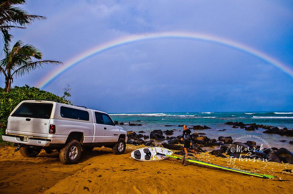 Windsurfer checking conditions, rainbow in background, Kauai, Hawaii