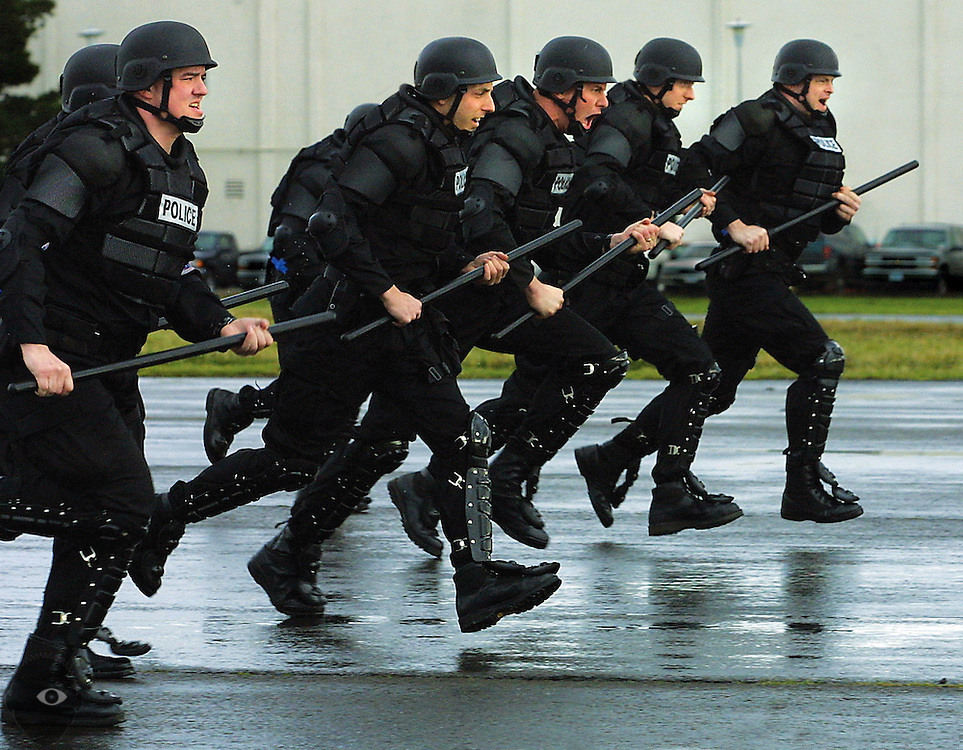 Portland Police Bureau's Rapid Response Team members charge up the runway Wednesday at the Coast Guard Air Base near Astoria. This is a drill called a dynamic approach in which officers rush towards the crowd and then form a barrier line.