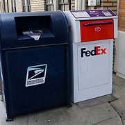 A Federal Express and US Postal Service drop boxes are seen outside a business in downtown Orlando on Monday, March 30, 2020 in Orlando, Florida. (Alex Menendez via AP)