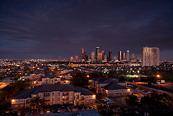 Western view of the Houston, Texas skyline with residential neighborhood in the foreground in the evening.