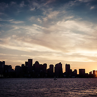 Boston skyline picture sunset with vintage retro tone. Scene includes downtown Boston city skyscraper buildings across Boston Harbor.