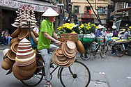 A man selling Vietnamese Conical straw hats and baskets from his bicycle in the Old Quarter, Hanoi, Vietnam, Southeast Asia
