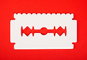 Big white ice scraper  shaped as razor blade with one sharp edge and one toothed edge isolated on red background.