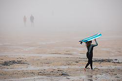 © Licensed to London News Pictures. 27/05/2020. Padstow, UK. Surfers walk along the beach at Harlyn Bay, Cornwall as a sea mist engulfs the beach. On Monday, a man died after getting into difficulty in the sea between nearby Constantine Bay and Treyarnon Bay. A teenage girl also died after being trapped in a capsized rigid inflatable boat near Padstow. Multiple other beach related incidents are being reported daily. Due to Coronavirus (COVID-19), the RNLI are currently not operating a Lifeguard service on the beaches in Cornwall, as there would be normally at this time of year. Photo credit : Tom Nicholson/LNP