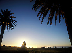 Couple talking beneath palm trees at dusk, Camps Bay, Cape Town, South Africa. (Credit Image: © Axiom/ZUMApress.com)