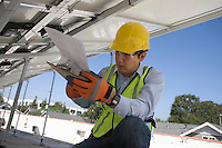 Maintenance worker refers to notes under solar panel in Los Angeles California