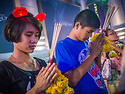 """31 DECEMBER 2012 - BANGKOK, THAILAND: Thais pray for a prosperous New Year on New Year's Eve at the Erawan Shrine in the Ratchaprasong Intersection in Bangkok. Many Thais go to Buddhist temples and shrines to """"make merit"""" for the New Year. The traditional Thai New Year is based on the lunar calender and is celebrated in April, but the Gregorian New Year is celebrated throughout the Kingdom, especially in larger cities and tourist centers, like Bangkok, Chiang Mai and Phuket. The Bangkok Countdown 2013 event was called ?Happiness is all Around @ Ratchaprasong.? All of the streets leading to Ratchaprasong Intersection were closed and the malls in the area stayed open throughout the evening.    PHOTO BY JACK KURTZ"""