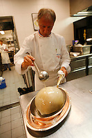 Chef Eric Frechon bastes the bladder containing the Poulard de Bresse with bouillion, to make it glisten and to keep it from getting too dry.. Hotel Bristol, Paris.....photo by Owen Franken
