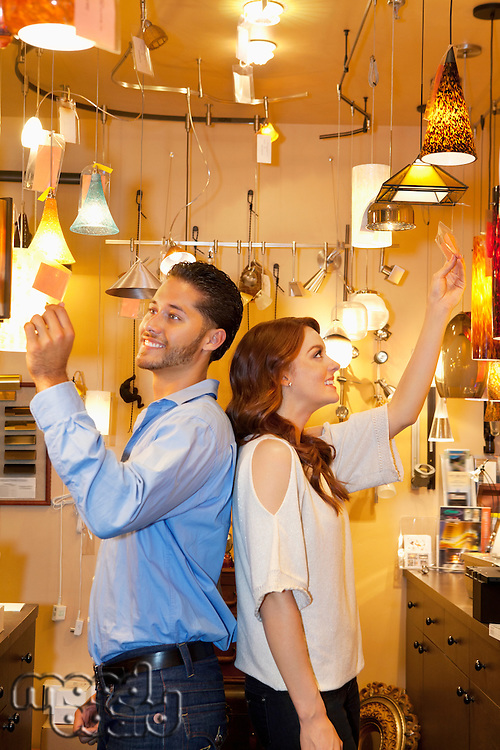 Happy young couple standing back to back while looking at price tag in lights store