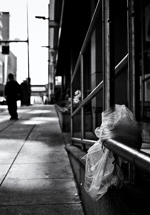 Shallow focus black and white image of a man standing on a sidewalk with a plastic bag tied to hand rail.