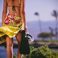 A woman carries snorkeling gear down to the beach in Hawaii