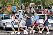 Aug. 8, 2009 -- SCOTTSDALE, AZ: People cross Scottsdale Rd during a protest against the Obama health care plan in Scottsdale, AZ.  Nearly 1,000 people opposed to the President Barack Obama's health care reform efforts picketed the offices of Congresman Harry Mitchell (D-AZ) in Scottsdale, AZ, Saturday. The protest was organized by conservative groups who are organizing similar protests against President Obama across the US. Ostensibly concerned mostly with health care reform, it was also a protest against almost everything related to the Obama administration. Photo by Jack Kurtz