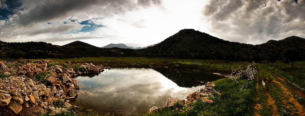 Capturing the reflections of the sky in a pool of water in a valley in Lassithi, Crete Greece.