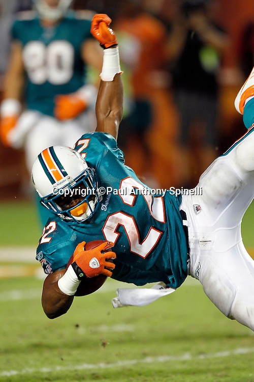 Miami Dolphins running back Reggie Bush (22) get upended as he runs the ball during the NFL week 1 football game against the New England Patriots on Monday, September 12, 2011 in Miami Gardens, Florida. The Patriots won the game 38-24. ©Paul Anthony Spinelli