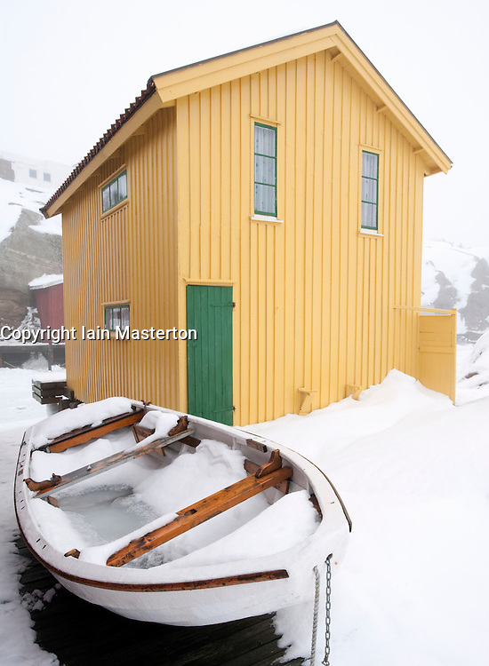 Yellow wooden boathouse in traditional fishing village of Smogen during winter after snow on Bohuslan coast in Sweden