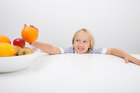 Little girl holding orange from fruit bowl at table