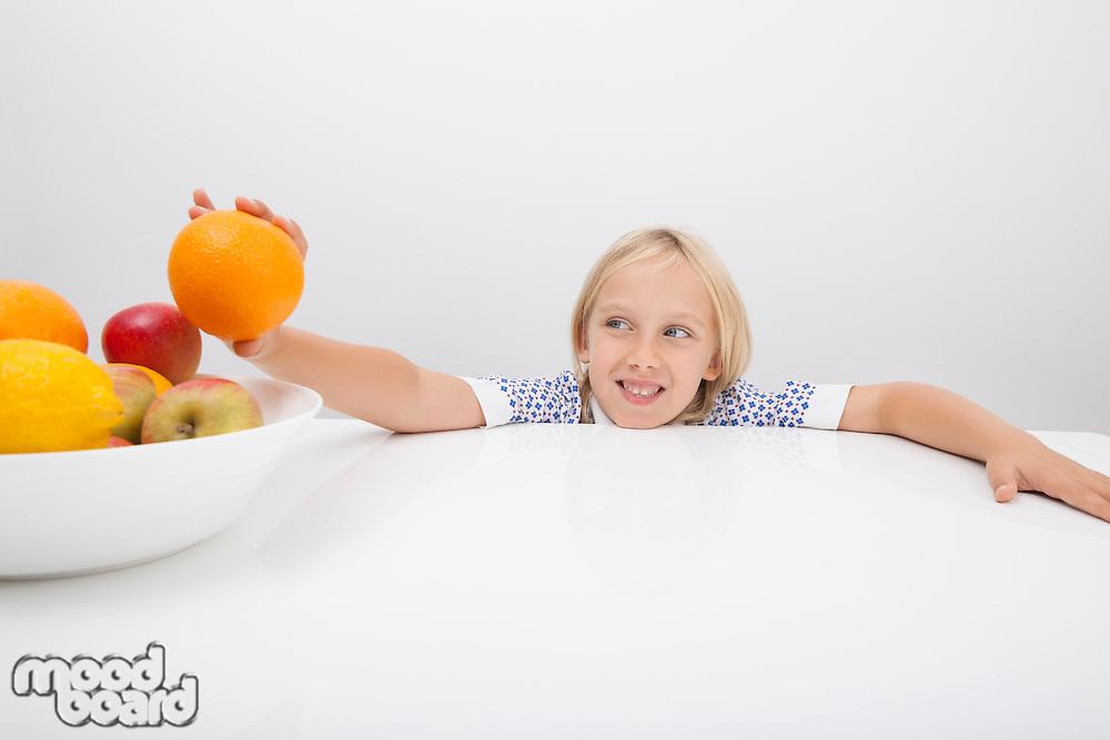 Little girl holding orange from fruit bowl at table