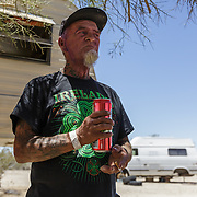 Jimmy Ray Silva, b. James Raymond Denny, has remains of the purple face paint he wore the night before playing guitar at The Range, in Slab City where he has lived year-round for five years. Musicians come from all over, as far as San Diego, to play on Saturday nights. Jimmy enjoys a beer at his best friend Donny's home, who served in the Army, as a special forces weapons expert in Somalia.