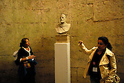 Tour guide explaining bust of Emperor Diocletian, one tourist standing nearby. Underground vaults, Palace of Diocletian, Split, Croatia