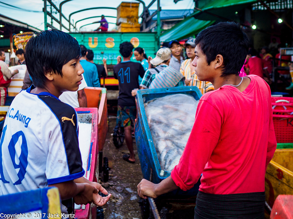 23 NOVEMBER 2017 - YANGON, MYANMAR: Workers stuck behind a truck in the San Pya Fish Market. San Pya Fish Market is one of the largest fish markets in Yangon. It's a 24 hour market, but busiest early in the morning. Most of the fish in the market is wild caught but aquaculture is expanding in Myanmar and more farmed fresh water fish is being sold now than in the past.    PHOTO BY JACK KURTZ