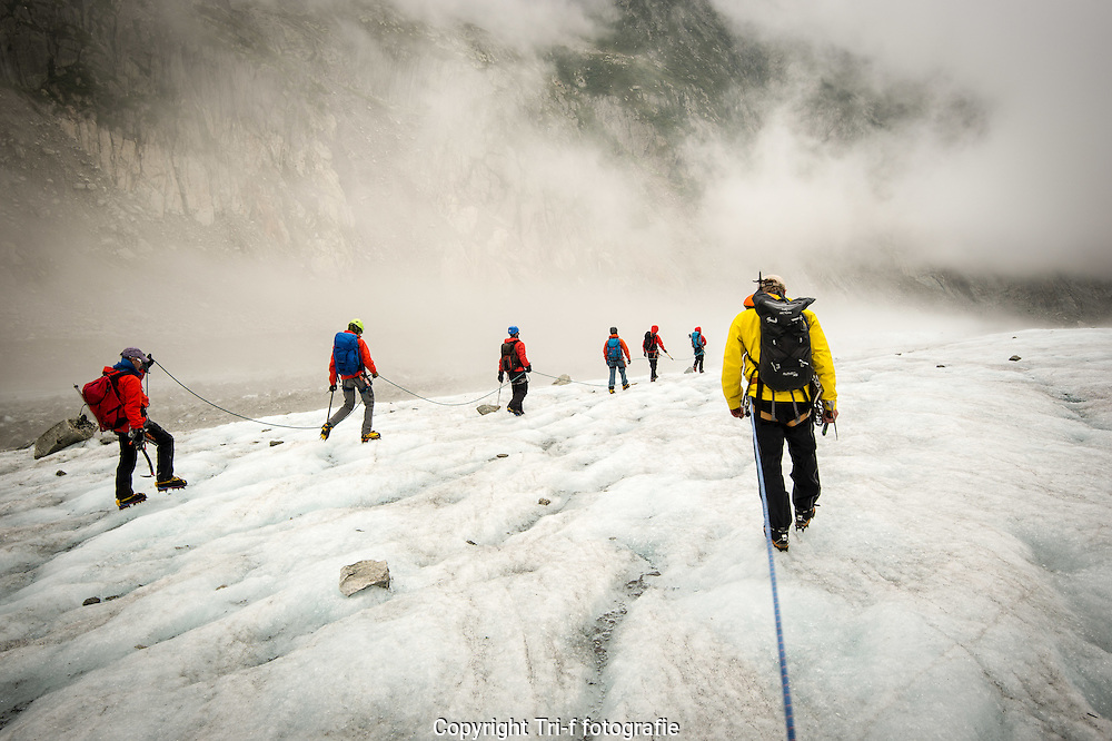 Mountain guides Steve and Sandy leading two groups across the Mer de Glace.