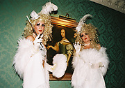 Two identically dressed women wearing white feathered evening wear blonde wigs and smoking with cigarette holders, Posh at Addington Palace, UK, August, 2004