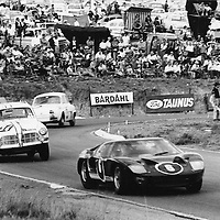 #6 Ford GT40 (Peter Sutcliffe) and #34 Team Lawson Volvo 122 S (Drivers - Frank Wingels and Jan Hettema) following through Clubhouse Corner, Kyalami 9-Hour Johannesburg South Africa 1965