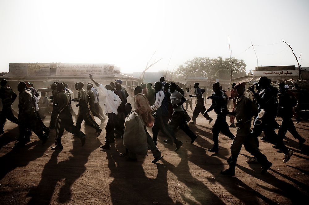 Members of the Sudanese Liberation Army run through the streets of Aweil in a training exercise. The central town of Aweil sits just below the hotly contested border between North and South Sudan. (© William B. Plowman)