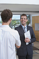 Male estate agent shaking hands with customer in new home