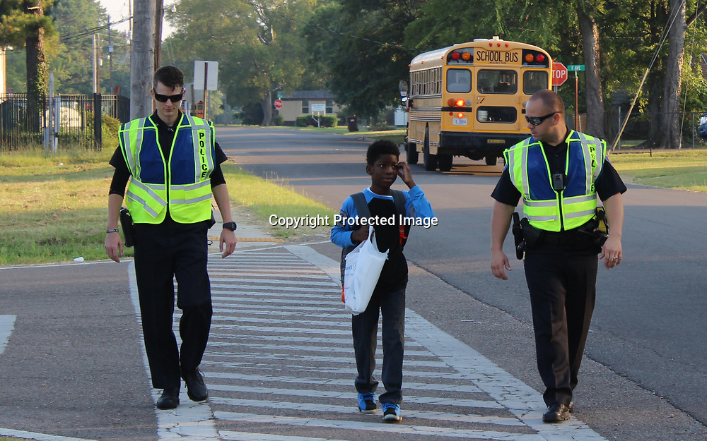 RAY VAN DUSEN/BUY AT PHOTOS.MONROECOUNTYJOURNAL.COM<br /> Amory police officers Jake Hall, left, and Johnny Hawkins walk a West Amory Elementary School student down a crosswalk during the first day of school. With the start of a new school year, the department has plans for enhanced school safety.