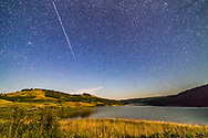 The International Space Station fades as it flies away to the east over Reesor Lake in the Cypress Hills of southeast Alberta. The ISS is fading as it enters the Earth&rsquo;s shadow and experiences sunset. Illumination of the ground is from the first quarter Moon off frame at right. <br /> <br /> This is a stack of 4 x 25-second exposures with the 14mm Rokinon lens and Canon 6D. This fuzzy spot at left is M31, Andromedia Galaxy.