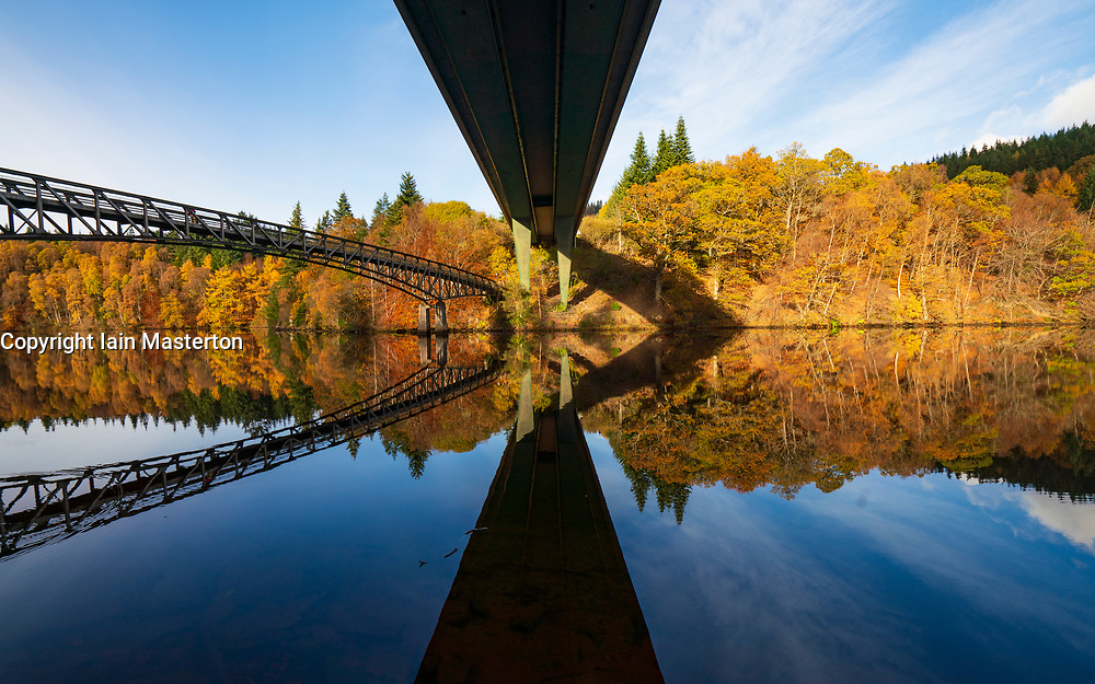 Spectacular late autumn tree colours and twin bridges are reflected in the waters of Loch Faskally in Pitlochry, Perthshire, Scotland, UK.