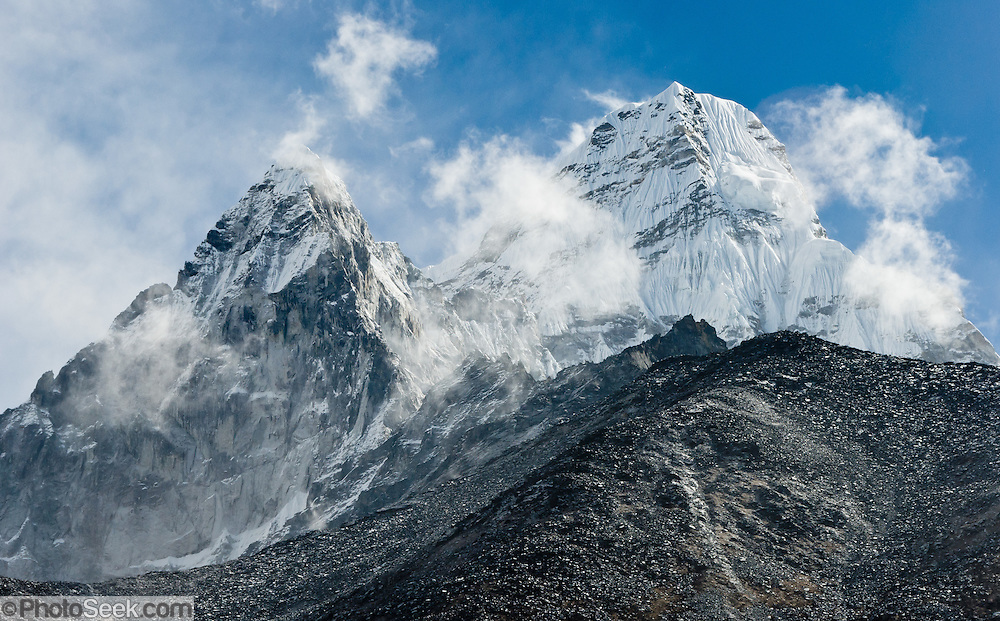 "Ama Dablam is a beautiful mountain, seen here near Pangboche, in the Himalaya range of eastern Nepal. The main peak is 22,349 feet (or 6,812 meters) tall, first climbed in 1961. The lower western peak is 18,251 feet (or 5,563 meters). Ama Dablam means ""Mother and Pearl Necklace"" (because the bulging hanging glacier is thought of as the pearl). For several days, Ama Dablam dominates the eastern sky for anyone trekking towards Everest Base Camp. Sagarmatha National Park was created in 1976 and honored as a UNESCO World Heritage Site in 1979."