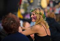 DEU, Deutschland, Germany, Berlin, 07.10.2019: Kundgebung der Aktivisten von Extinction Rebellion (XR) mit einer Strassenblockade am Potsdamer Platz. Die Umweltschützer wollen mit zahlreichen Aktionen und Blockaden in der Stadt auf ihr Anliegen einer strengeren Klimapolitik aufmerksam machen. Hier eine Teilnehmerin der Sitzblockade mit dem Logo der XR-Bewegung, einer Sanduhr in einem Kreis, auf der Wange.