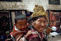 April 1985, Lhasa, Tibet Autonomous Region, China --- Elderly Tibetan Woman With Child on Back --- Image by © Owen Franken/CORBIS